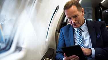 Geschäftsmann in blauem Anzug mit Tablet im Flugzeug