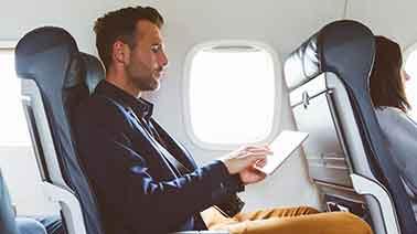 Geschäftsmann mit Tablet im Flugzeug