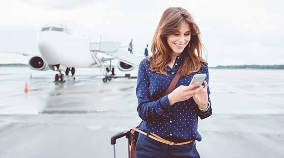 Frau am Flughafen mit Smartphone