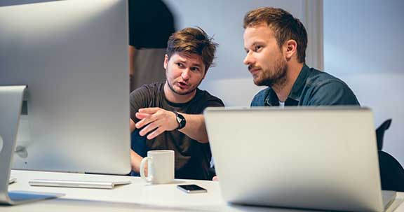 Two young men working together in office.