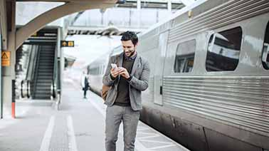 Geschäftsreisender am Bahnsteig mit Smartphone